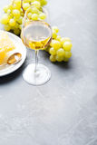 Glass of white wine and assorted cheese with grape on a slate background Copy space Royalty Free Stock Photo