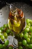 A glass of white wine on a background of grapes. High speed wine stock image