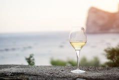 A glass of white wine, on background the sea of Massalubrense near Sorrento Stock Photo