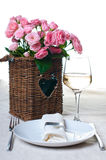 Glass of white wine and a basket of roses Royalty Free Stock Photo