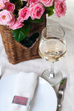 Glass of white wine and a basket of roses Stock Photos