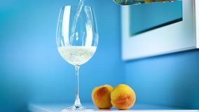 A glass of white wine on a blue background is standing on a white table with two peaches stock video