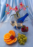 Glass of white wine and blue bottle with fruits Stock Photo