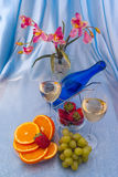 Glass of white wine and blue bottle with oranges Royalty Free Stock Image