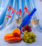 Glass of white wine and blue bottle with oranges Royalty Free Stock Images