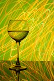A glass of white wine on a blurred colored background Stock Photography