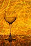 A glass of white wine on a blurred colored background Royalty Free Stock Photo