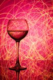 A glass of white wine on a blurred colored background Stock Images