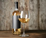 Glass of white wine and bottle with blank label. On wooden table. Mock up for design Stock Photo