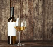Glass of white wine and bottle with blank label. On wooden table. Mock up for design royalty free stock image