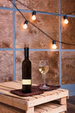 Glass of white wine and bottle in modern loft interior with light garland on wooden wall. Stock Images