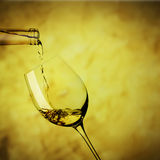 Glass of white wine. From a bottle to a glass of red wine in slightly inclined Royalty Free Stock Photo