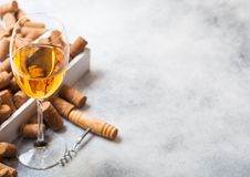 Glass of white wine with box of corks and crkscrew opener on stone kitchen table background. Top view. Space for text stock photography