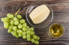 Glass of white wine, bunch of grape and cheese Royalty Free Stock Images