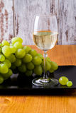 Glass of white wine and a bunch of grapes. Stock Photography
