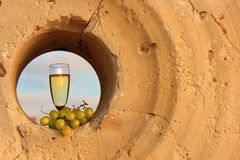 Glass of white wine and a bunch of grapes inside the a millstone. In the National Park Achziv, Israel royalty free stock images