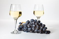 A glass of white wine. Bunch of grapes on a white background stock photography