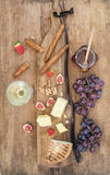Glass of white wine, cheese board, grapes, figs, strawberries, honey and bread sticks on rustic wooden background Royalty Free Stock Photos