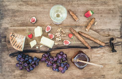 Glass of white wine, cheese board, grapes, figs, strawberries, honey and bread sticks on rustic wooden background Stock Photo