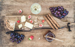 Glass of white wine, cheese board, grapes, figs, strawberries, honey and bread sticks on rustic wooden background Royalty Free Stock Images