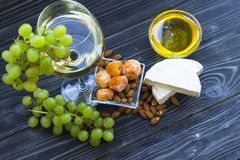 A glass of white wine with cheese cuts, figs, nuts, honey, grapes on a dark rustic wooden boards background. Top view stock images