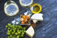 A glass of white wine with cheese cuts, figs, nuts, honey, grapes on a dark rustic wooden boards background. Top view royalty free stock image