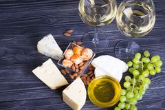 A glass of white wine with cheese cuts, figs, nuts, honey, grapes on a dark rustic wooden boards background. Top view stock photos