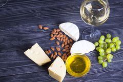 A glass of white wine with cheese cuts, figs, nuts, honey, grapes on a dark rustic wooden boards background. Top view royalty free stock photo