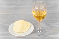Glass of white wine and cheese in dish on table Royalty Free Stock Photos