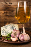 Glass of white wine, cheese, garlic and spices Royalty Free Stock Images