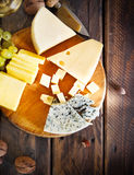 Glass of white wine, cheese, nuts and grapes Stock Images