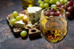 Glass of white wine, cheeseboard and fruit on dark background. Closeup, horizontal Royalty Free Stock Photo