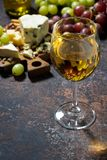 Glass of white wine, cheeseboard and fruit on dark background. Vertical, closeup Royalty Free Stock Image