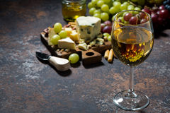 Glass of white wine, cheeseboard and fruit on dark background Royalty Free Stock Image