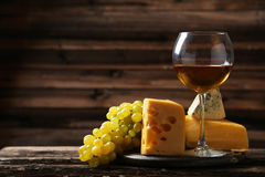 Glass of white wine, cheeses and grapes on brown wooden background Royalty Free Stock Photos