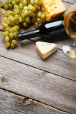 Glass of white wine, cheeses and grapes on the grey wooden background Stock Photos
