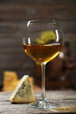 Glass of white wine and cheeses on the grey wooden background Stock Photos