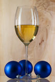 Glass of white wine and Christmas decoration Royalty Free Stock Photography