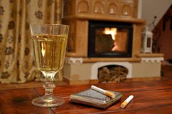 Glass of white wine, cigarettes and snuffbox. On wooden table ahead fireplace Stock Image