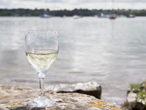 Glass of white wine by the coast Stock Photos