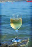 Glass of white wine by the coast Royalty Free Stock Photos