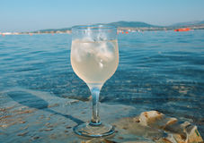 Glass of white wine by the coast. On the rocks, washed by the waves of the sea royalty free stock image