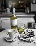 A glass of white wine, cup, chocolate cake and a bottle of wine on a retro background stock photos
