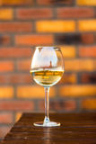 Glass with white wine on the desk, brick background. Glass with white wine on the desk, the brick background stock image
