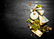 Glass of white wine with different cheeses , grapes and nuts. Royalty Free Stock Photography