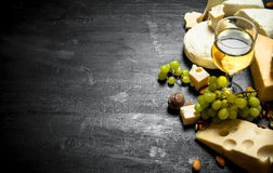 Glass of white wine with different cheeses , grapes and nuts. Stock Image