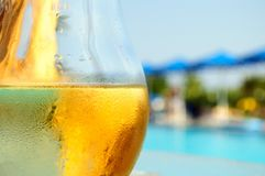 Glass of white wine on the edge of the swimming pool stock images