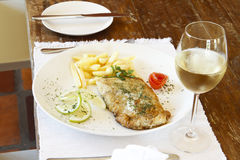 Glass of white wine with fish and chips Royalty Free Stock Images