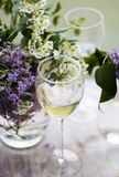 Glass of white wine and flowers stock image
