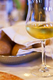 Glass of white wine and fresh bread in restaurant Stock Images